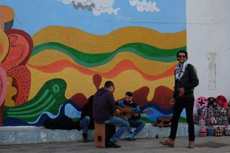 Grafitis y unos chicos tocando y contando. Marrueocs